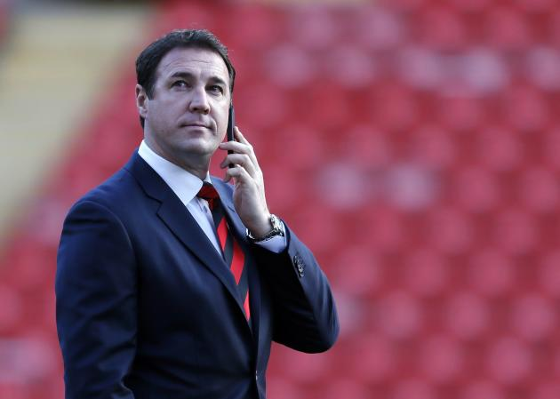 Cardiff City's manager Mackay talks on a mobile phone before their English Premier League soccer match against Liverpool at Anfield in Liverpool