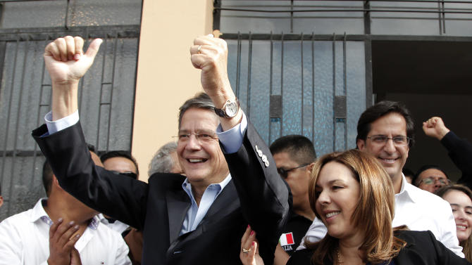 Presidential candidate Guillermo Lasso of the Creating Opportunities Party ( CREO ), left, gestures to supporters as he stands next to next to his wife Maria de Lourdes Alcivar, second from right,  at a polling station where he accompanied his running mate Juan Carlos Solines, right, to vote in Quito, Ecuador, Sunday, Feb. 17, 2013.  Lasso, a former Banco de Guayaquil executive president,  is the leading opponent to President Rafel Correa who is highly favored to win a second re-election. Ecuadoreans  elect president,  vice-president and National Assembly members Sunday.(AP Photo/Dominique Riofrio)