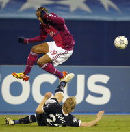 Lyon's Jimmy Briand, top, is challenged by Dinamo Zagreb's Domagoj Vida during the Champions League group D soccer match between Dinamo Zagreb and Lyon, in Zagreb, Croatia, Wednesday, Dec. 7, 2011. (AP Photo/Darko Bandic)
