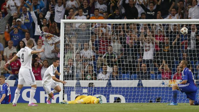 Real Madrid's James Rodriguez, centre, scores his side's fourth goal during the Champions League Group B soccer match between Real Madrid and Basel at the Santiago Bernabeu stadium in Madrid, Spain, Tuesday Sept. 16, 2014. (AP Photo/Daniel Ochoa de Olza)