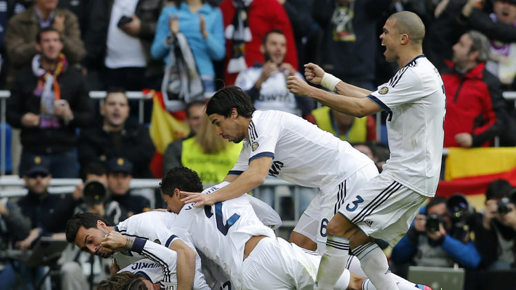Real Madrid players celebrate after Sergio Ramos, partly seen scored the winning goal against Barcelona during a Spanish La Liga soccer match at the Santiago Bernabeu stadium in Madrid, Saturday March 2, 2013. Real Madrid won the game 2-1.(AP Photo/Paul White)