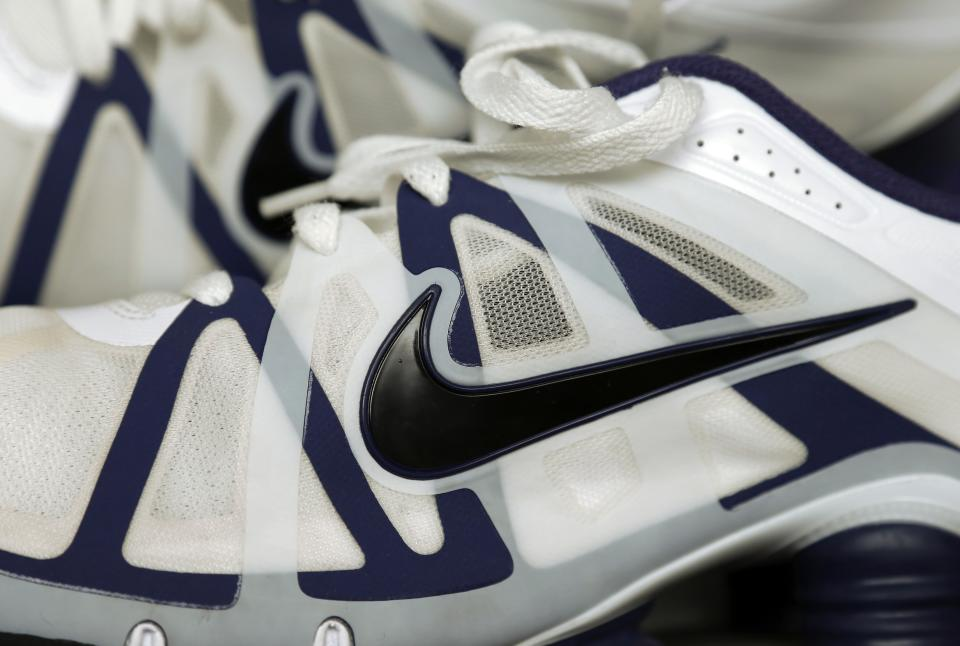 Nike falls as co. tamps down 2014 profit outlook