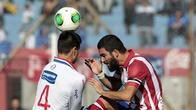 Guillermo de los Santos (L) of Uruguay's Nacional and Arda Turan of Spain's Atletico Madrid fight for the ball during a friendly match in Montevideo, August 4, 2013 (Reuters)
