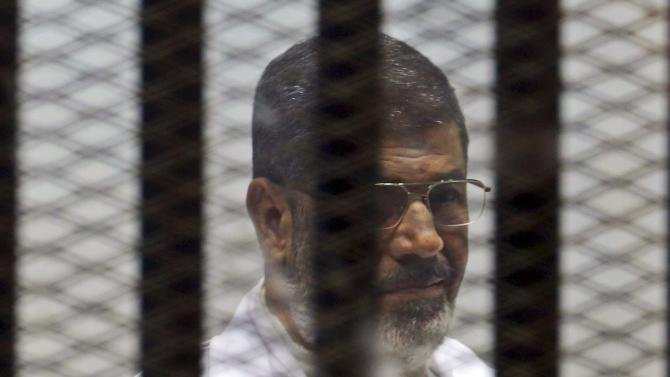 Former Egyptian President Mohamed Mursi sits behind bars with other Muslim Brotherhood members at a court in the outskirts of Cairo