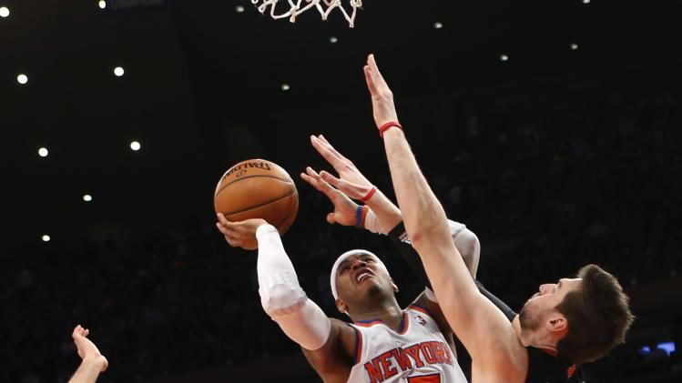 New York Knicks' Anthony drives into the defense of Toronto Raptors' Bargnani during their NBA basketball game in New York