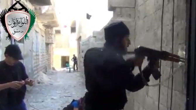 "In this image taken from video obtained from the Ugarit News, which has been authenticated based on its contents and other AP reporting, Syrian rebels clash with government forces in Damascus, Syria, Friday, May 3, 2013. Syria's main opposition group on Friday accused President Bashar Assad's regime of committing a ""large-scale massacre"" in a Sunni village near the Mediterranean coast, killing scores of people, according to activists. (AP Photo/Ugarit News via AP video)"