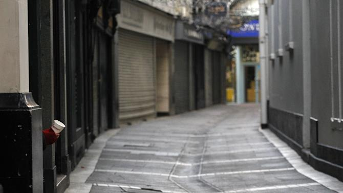 A man takes shelter in a doorway, left, as he begs for money on a deserted street in central Dublin, Ireland, Friday, Nov. 19, 2010. The euro is continuing to rise modestly against the dollar amid hopes of a resolution to Ireland's debt crisis. Ireland appears headed toward taking a loan from the European Union to bolster its debt-crippled banks, helping take the edge off recent fears about the resurgence of Europe's debt troubles.  (AP Photo/Peter Morrison)