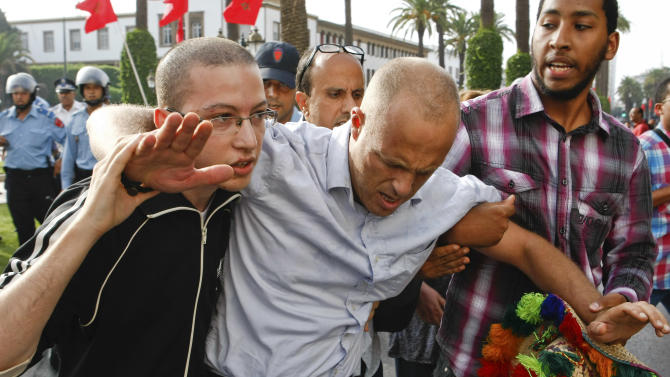 """Activists help a friend injured during a protest outside parliament against annual ceremony allegiance to King Mohammad VI """"celebration of loyalty"""" that activists have criticized as """"backward"""" in Rabat, Wednesday Aug 22, 2012. Activists have denounced the ceremony, which some say reflects an """"ignorance and backwardness"""" in Morocco that is inappropriate for the 21st century. (AP Photo/Abdeljalil Bounhar)"""