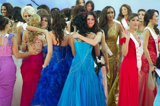 A photo taken on August 18, 2012 shows Miss World 2012 contestants as they console each other following the pageant's final ceremony at the Dongsheng stadium in the inner Mongolian city of Ordos. Chin