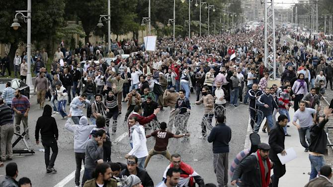 Egyptian President Mohammed Morsi's supporters, background, clash with opponents, foreground, outside the presidential palace, in Cairo, Egypt, Wednesday, Dec. 5, 2012. Wednesday's clashes began when thousands of Islamist supporters of Morsi descended on the area around the palace where some 300 of his opponents were staging a sit-in. (AP Photo/Hassan Ammar)