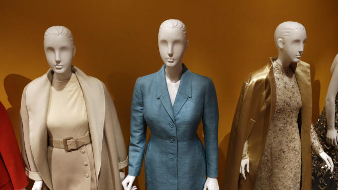 """An Oscar de la Renta pantsuit, center, worn by Former first lady Hillary Rodham Clinton, is displayed next to other creations by the designer at the Clinton Presidential Library in Little Rock, Ark., Monday, July 8, 2013. The """"Oscar de la Renta: American Icon"""" exhibit is on display at the Clinton library until Dec. 1. (AP Photo/Danny Johnston)"""