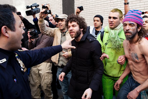 An Occupy Wall Street demonstrator is pushed back from the scene of an arrest by a police officer after a march in celebration of the protest's sixth month, Saturday, March 17, 2012, in New York. With