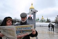 "A couple reads a Ukrainian newspaper bearing a headline that says ""Day and night of voting"" in Kiev. Ukraine's ruling party was set Monday to beat the allies of jailed ex-premier Yulia Tymoshenko in legislative elections that observers condemned as a setback for the ex-Soviet state's nascent democracy"