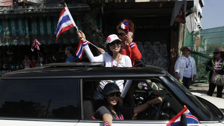 Anti-government protesters wave Thai national flags as they join a march during a rally at a major business district in Bangkok