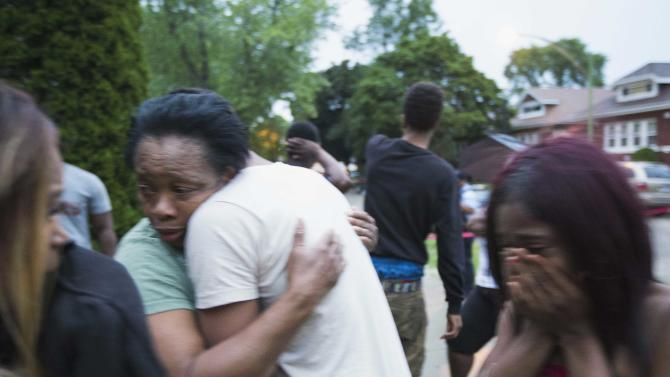 In this Saturday, July 5, 2014 photo, Georgia Utendahl, left, and Shanice Smith, right, grieve after learning that their family member was shot by police on Chicago's South Side. The Fourth of July weekend was a bloody one in Chicago, where at least nine people were shot to death and at least 60 others were wounded. (AP Photo/Sun-Times Media, Alex Wroblewski) MANDATORY CREDIT, MAGS OUT, NO SALES
