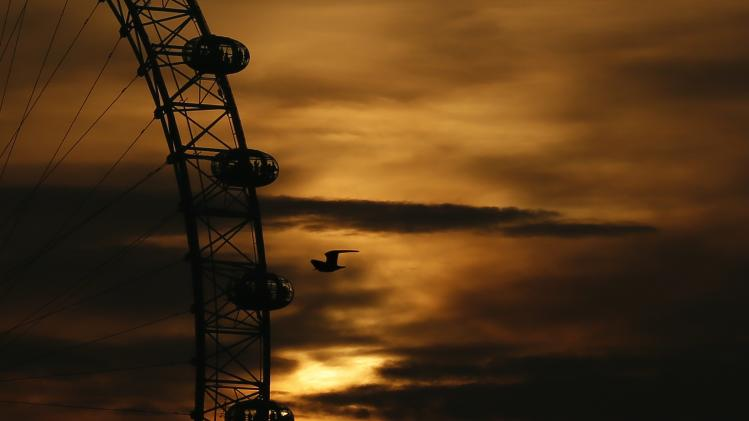 The sun sets behind the London Eye in central London