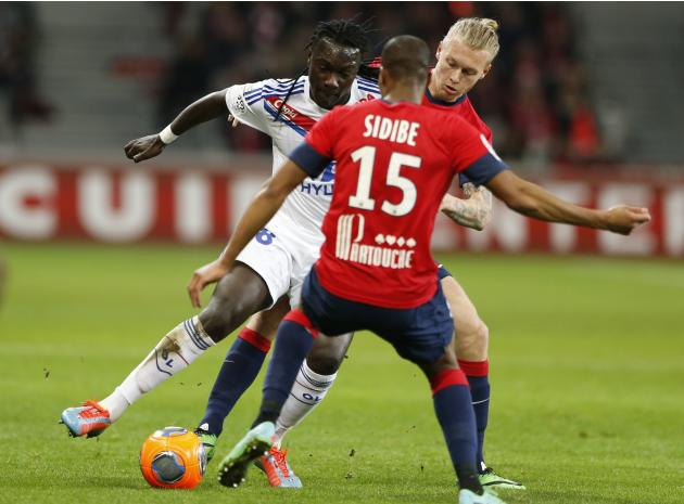 Lille's Kjaer and Sidibe fight for the ball with Lyon's Gomis during their French Ligue 1 soccer match at Pierre Mauroy Stadium in Villeneuve d'Ascq