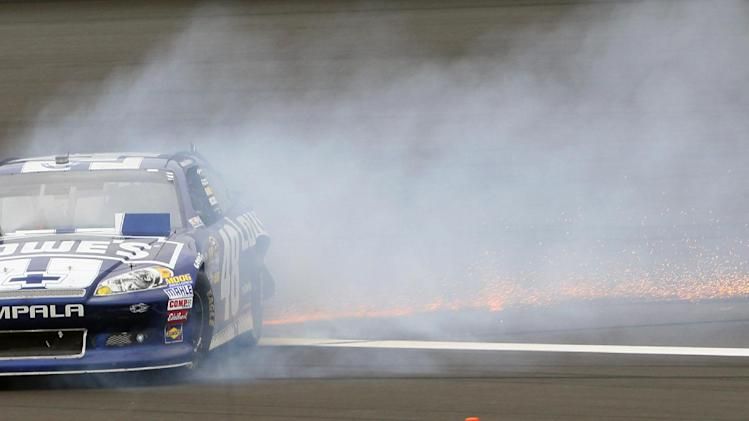 Jimmie Johnson spins after hitting the wall during a NASCAR Sprint Cup Series auto race at Kansas Speedway in Kansas City, Kan., Sunday, Oct. 21, 2012. (AP Photo/Colin E. Braley)