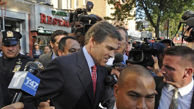 Republican presidential candidate Texas Gov. Rick Perry heads to his vehicle without stopping as he exits the Papasito Restaurant in the Inwood section of Manhattan, Monday, Sept. 19, 2011, in New York. (AP Photo/Louis Lanzano)