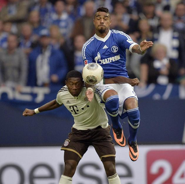 Bayern's David Alaba of Austria, left, and Schalke's Kevin-Prince Boateng of Ghana challenge for the ball during the German soccer Bundesliga match between FC Schalke 04 and Bayern Munich at the arena