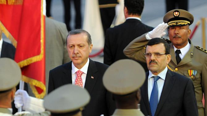 Tunisian Prime Minister Ali Larayed, 2nd right, greets his Turkish counterpart Recep Tayyip Erdogan, facing camera left, at the Airport of Tunis Carthage, Tunis, Wednesday, June 5, 2013.  In Turkey thousands of union members on a two-day strike marched into Istanbul's landmark Taksim Square and central Ankara in a show of support for protesters angry at what they see as Recep Tayyip Erdogan's increasingly authoritarian rule. Police used tear gas and water cannons to break up the gathering in Ankara after allowing demonstrations to continue for some eight hours. (AP Photo/Hassene Dridi)