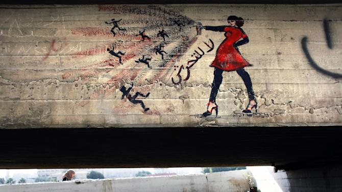 """In this Thursday, Oct. 4, 2012 file photo, an Egyptian woman walks by a mural with Arabic that reads """"no for harassing women,"""" in Cairo, Egypt. Graffiti has been among the most powerful art forms and tools of Egypt's revolution and the turbulent months since, but it also has proven to be its most vulnerable and ephemeral. So a group of artists, photographers and a publisher joined hands to preserve the images. """"Wall Talk"""" _ their newly released, 680-page book _ collects hundreds of photos of graffiti dating from the Jan. 25, 2011 eruption of the revolt against then-President Hosni Mubarak until today. (AP Photo/Nasser Nasser)"""