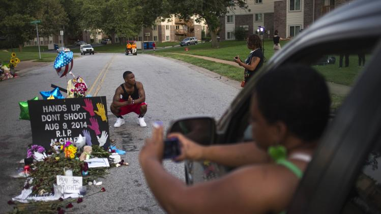 A woman stops to take photos from her vehicle as a nearby resident puts his hands together in prayer while posing for photographs at a makeshift memorial for Michael Brow in Ferguson