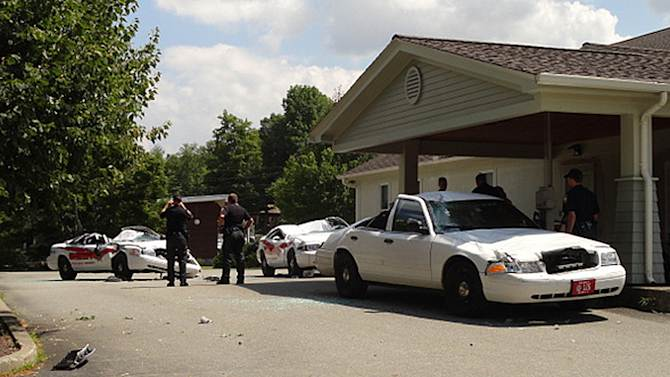 Sheriff officers examine crushed cruisers at the Orleans County Sheriff's Department in Newport, Vt., Thursday, Aug. 2, 2012. Authorities say 34-year old Vermont farmer Roger Pion, angry over a recent arrest last month on charges of resisting arrest and marijuana possession, used a large tractor like a monster truck, destroying seven police cruisers. (AP Photo/Northland Journal, Scott Wheeler)