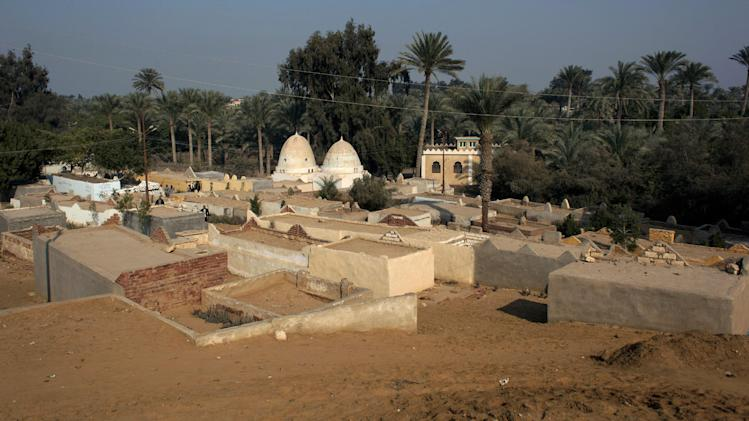 This Sunday, Jan. 13, 2013 photo, shows the local cemetery of the ancient historic site of Dahshour, Egypt. The illegal expansion of a local cemetery has raised a panic among antiquities experts, who warn that the construction endangers the ancient, largely unexplored complex of Dahshour. The tombs are small complexes on their own, build mainly of cheap white bricks: Each is a walled courtyard with multiple enclosed niches where multiple family members can be buried. Rows of them now cover several acres inside the UNESCO-defined antiquities zone of Dahshour, coming to within 150 meters (yards) of Sneferu's Valley Temple. (AP Photo/Nasser Nasser)