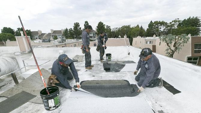 Roofers with Hull Brothers Roofing & Waterproofing resurface townhomes roofs at the Marina del Rey seaside community of Los Angeles on Tuesday, Aug. 25, 2015. While drought-plagued California is eager for rain, the forecast of a potentially Godzilla-like El Nino event has communities clearing out debris basins, urging residents to stock up on emergency supplies and even talking about how a deluge could affect the 50th Super Bowl. (AP Photo/Damian Dovarganes)