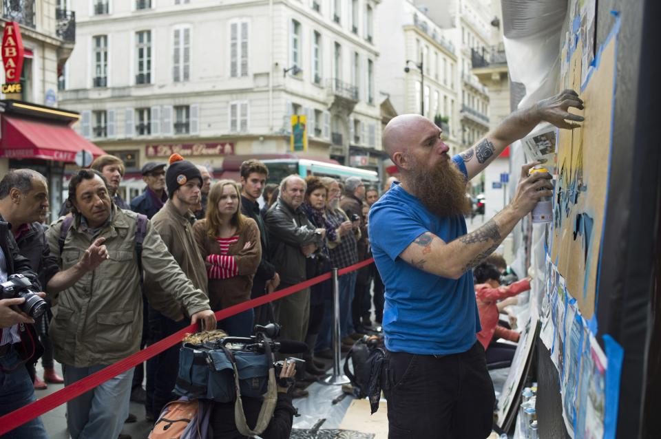 US artist Logan Hicks, draws a painting in the street outside Drouot auction house, in Paris, Thursday Oct.24, 2013. This painting is one among dozens of art pieces from street artists which will be auctioned Friday Oct. 25. (AP Photo/Thibault Camus)