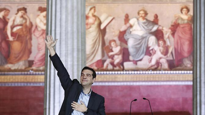 """Leader of Syriza left-wing party Alexis Tsipras waves to his supporters outside Athens University Headquarters, Sunday, Jan. 25, 2015. A triumphant Alexis Tsipras told Greeks that his radical left Syriza party's win in Sunday's early general election meant an end to austerity and humiliation and that the country's regular and often fraught debt inspections were a thing of the past. """"Today the Greek people have made history. Hope has made history,"""" Tsipras said in his victory speech at a conference hall in central Athens. (AP Photo/Petros Giannakouris)"""