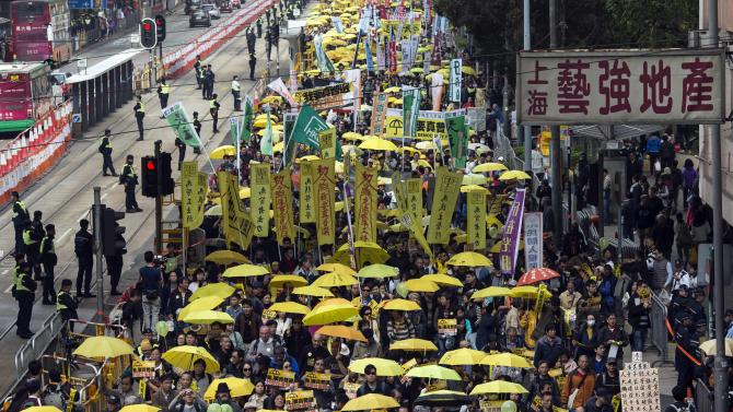 Thousands of pro-democracy protesters hold up yellow umbrellas, symbols of the Occupy Central movement, during a march in the streets to demand universal suffrage in Hong Kong