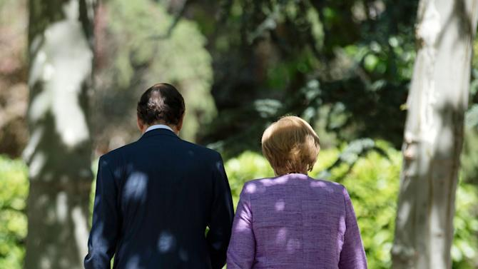 Spain's Prime Minister Mariano Rajoy, left, walks with German Chancellor Angela Merkel  prior to a  a news conference at the Moncloa Palace, in Madrid, Thursday, Sept. 6, 2012. (AP Photo/dapd/Oliver Lang))