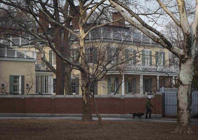 A man and a dog walk past Gracie Mansion in New York