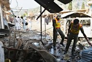Pakistani security officials inspect wreckage at the site of a suicide bomb attack in Darra Adam Khel. A suicide bomber on Saturday blew up a car at a crowded market in a northwestern Pakistani tribal town, killing at least 16 people and wounding 30 others, officials said
