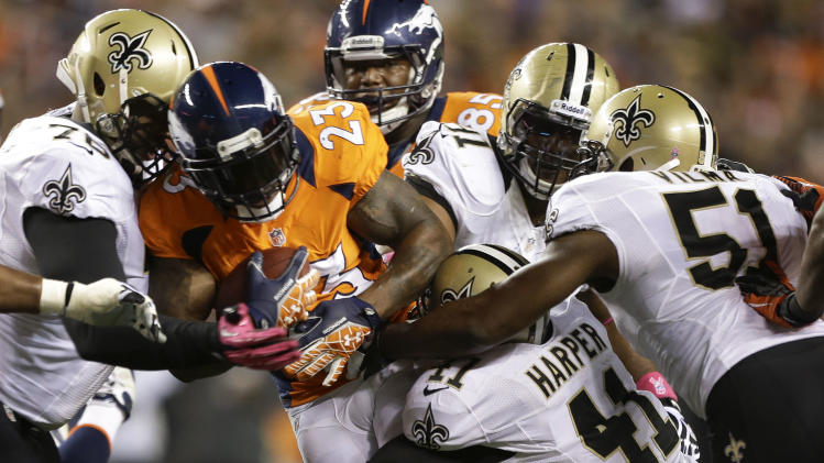 Denver Broncos running back Willis McGahee (23) is tackled by the New Orleans Saints in the first quarter of an NFL football game, Sunday, Oct. 28, 2012, in Denver. (AP Photo/Jack Dempsey)
