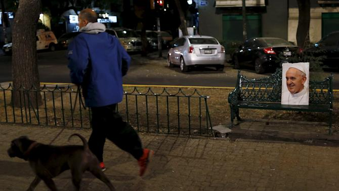 A man jogs with a dog on a pathway next to a poster with a picture of Pope Francis on a bench, before his upcoming visit to Mexico City