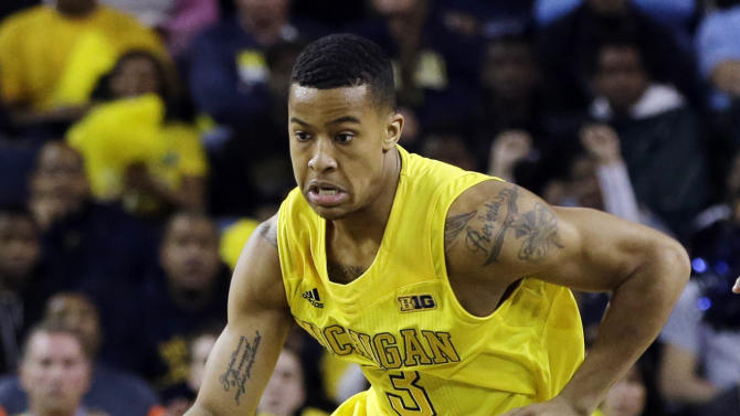 FILE - In this March 3, 2013, file photo, Michigan guard Trey Burke (3) dribbles upcourt during the first half of an NCAA college basketball game against Michigan State in Ann Arbor, Mich. Burke, the sophomore point guard who led Michigan to the Final Four, has been selected The Associated Press' college basketball player of the year on Thursday, April 4, 2013. (AP Photo/Carlos Osorio, File)