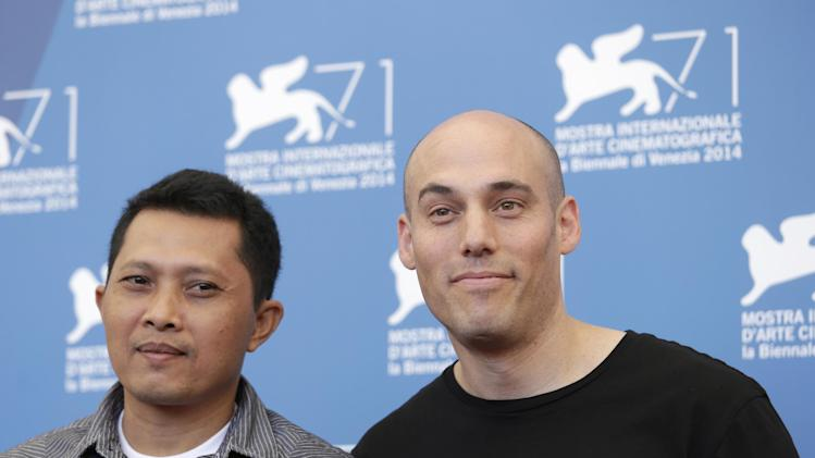 Actor Adi Rukun, right, and director Joshua Oppenheimer pose for photographers at the photo call for the film The Look of Silence the 71st edition of the Venice Film Festival in Venice, Italy, Thursday, Aug. 28, 2014. (AP Photo/David Azia)