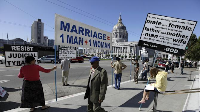 FILE - This Sept. 6, 2011 file photo shows a man walking past a group of people protesting against gay marriage outside a courtroom where the California Supreme Court was hearing arguments in San Francisco. The Obama administration is quietly considering urging the Supreme Court to overturn California's ban on gay marriage, a step that could be a major political victory for advocates of same-sex unions.  (AP Photo/Eric Risberg, File)