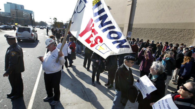 Chuck Helms, of Nutley, N.J., holds a union flag as he joins a large gathering to protest against Wal-Mart on Black Friday, Nov 23, 2012, in Secaucus, N.J.  Wal-Mart employees and union supporters are taking part in today's nationwide demonstration for better pay and benefits. A union-backed group called OUR Walmart, which includes former and current workers, staged the demonstrations and walkouts at hundreds of stores on Black Friday, the day when retailers traditionally turn a profit for the year. (AP Photo/Mel Evans)