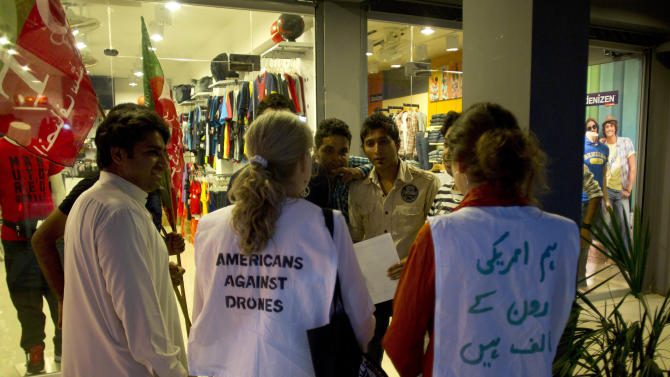 """American citizens invite people to join anti-drone rally to Pakistani tribal area, in Islamabad, Pakistan, Friday, Oct. 5, 2012. A group of American anti-war activists are in Pakistan with plans to join a """"march"""" into the country's tribal belt to protest U.S. drone strikes in the rugged northwest territory. Their presence has energized some Pakistanis, but it also has added to concerns that Islamist militants will target the weekend event. Writing on a vest, right,  reads """"we, Americans are against drones."""" (AP Photo/B.K. Bangash)"""