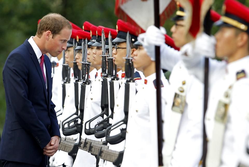 Prince William, the Duke of Cambridge, left, stops to talk to an honor guard member during the welcome ceremony at the Istana, or Presidential Palace, on Tuesday Sept. 11, 2012 in Singapore. The Duke and Duchess of Cambridge started an official three-day trip to Singapore Tuesday. (AP Photo/Wong Maye-E)