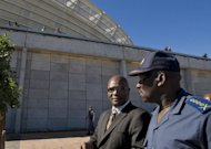 South African Minister of Police Nathi Mthethwa (L) and National Commissioner General Bheki Cele talk outside Cape Town stadium. Mthethwa said murders had continued a downward trend since the end of apartheid in 1994.