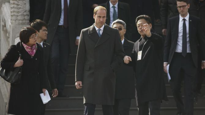 Britain's Prince William is accompanied by a museum officer during a visit to the Forbidden City in Beijing