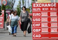 Pedestrians walk past an exchange office&#39;s rates notice in Bucharest August 10. The recovery in Romania&#39;s economy after two years of severe recession is now coming under threat, analysts warn, victim to the months-long political crisis that has engulfed the EU country