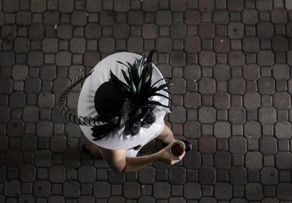 A spectator walks to the grand stands before the 138th Kentucky Derby horse race at Churchill Downs Saturday, May 5, 2012, in Louisville, Ky. The Run for the Roses draws them to Churchill Downs. But what race goers wear is as much a spectacle in itself. (AP Photo/Matt Slocum)