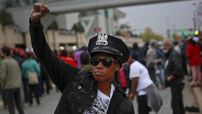 A protester wears a Baltimore police department hat taken out of a police car that was damaged during a rally to protest the death of Freddie Gray who died following an arrest in Baltimore, Maryland