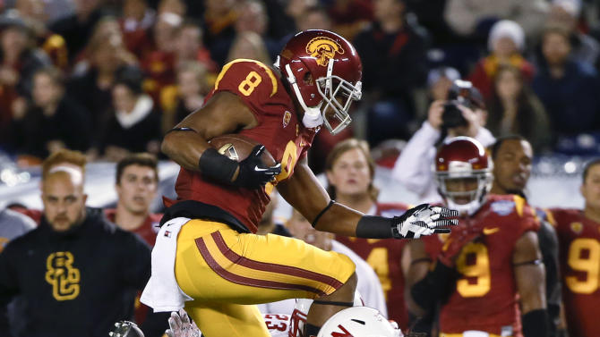 Southern California wide receiver George Farmer hurdles Nebraska safety Corey Cooper, right, and cornerback Daniel Davie during the first half of the Holiday Bowl NCAA college football football game Saturday, Dec. 27, 2014, in San Diego. (AP Photo/Lenny Ignelzi)